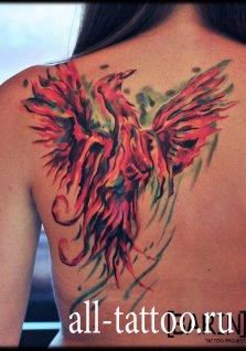 Женская татуировка на спине в виде птицы
