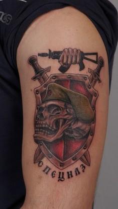 Татуировка на плече — череп на фоне цветного щита и меча с надписью «Спецназ»