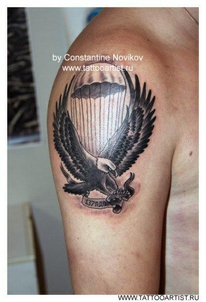 Тату на плече летящего орла на фоне парашюта